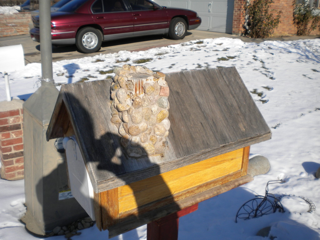What creature lives in this mailbox with a chimney?