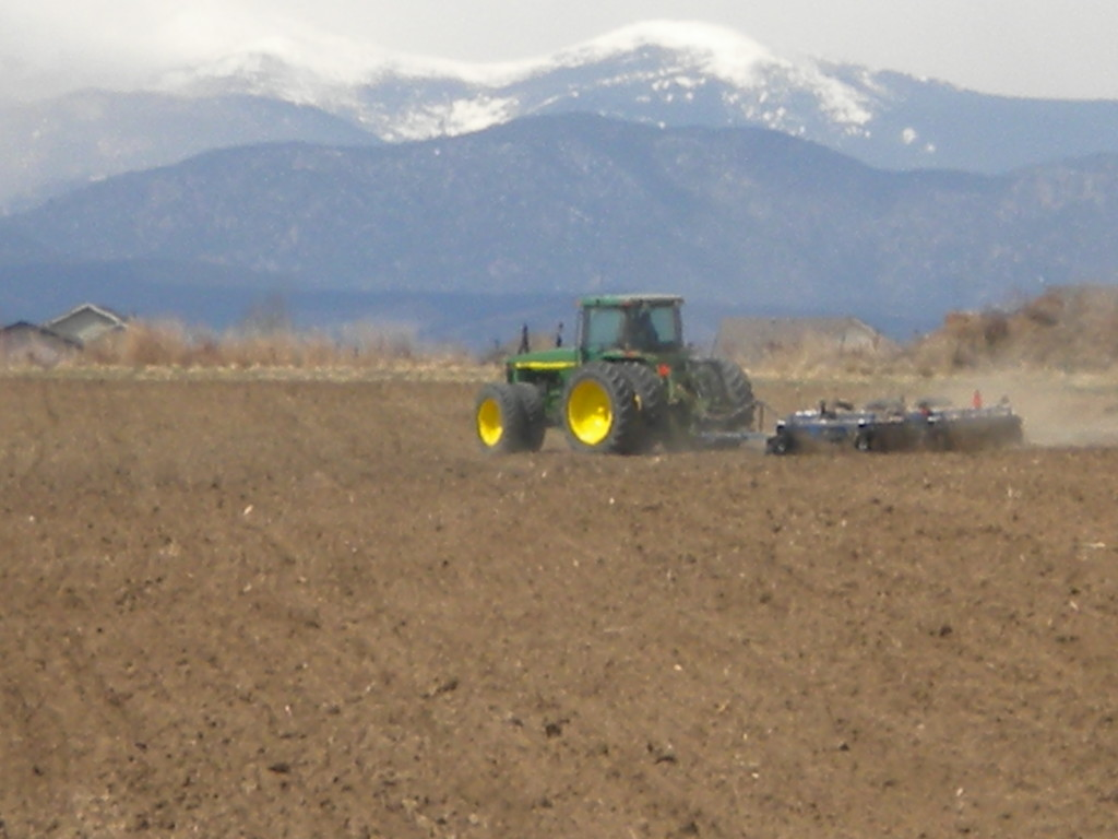 Plowing with the mountains looming in the distance