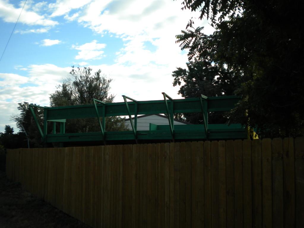 large backyard skateboard ramp peeking over fence