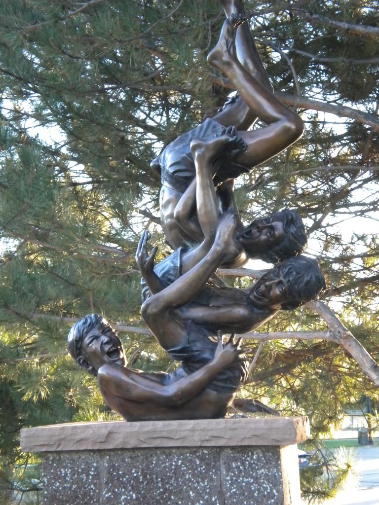 sculpture at park entrance --- kids having fun