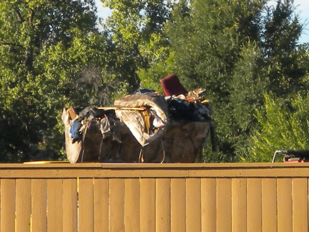 loader dumping trash across the tracks at the storage units