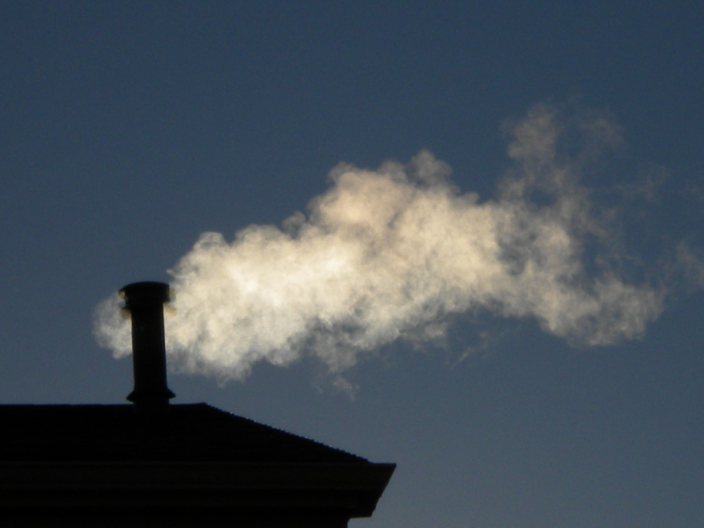 Chimney smoke in the early morning sun